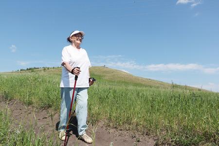 Nordic Walking - elderly woman is hiking Stock Photo