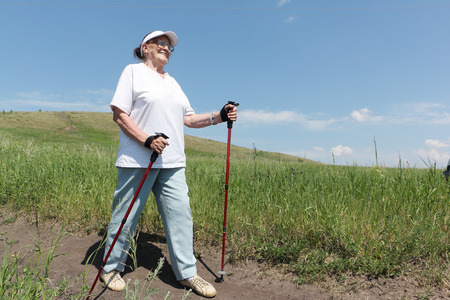 Nordic Walking - elderly woman is hiking Stock Photo