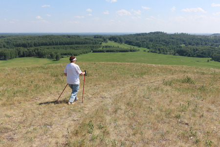 the great grandmother: Nordic Walking - elderly woman is hiking  in the summer