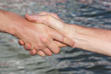 parting the sea: Suntanned male hands make handshake against a water surface Stock Photo