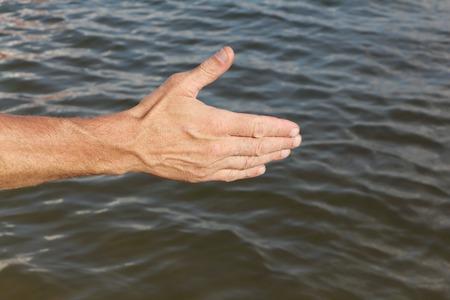 Suntanned mano maschile contro una superficie dell'acqua