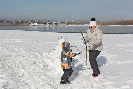 The woman in a light jacket and the little boy building a snowman on the river bank in the winter Stock Photo