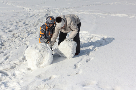 The woman in a light jacket and the little boy doing a snowball for construction of a snowman