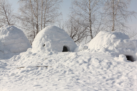 orifice: Snow construction an igloo standing on a winter glade