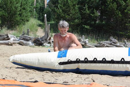 river rafting: The man with a beard prepares a catamaran for a river rafting