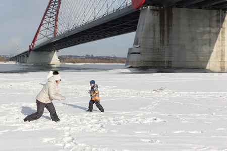 palle di neve: La donna e piccole palle di neve ragazzo che giocano sulla riva del fiume in inverno, fiume Ob, Russia Archivio Fotografico