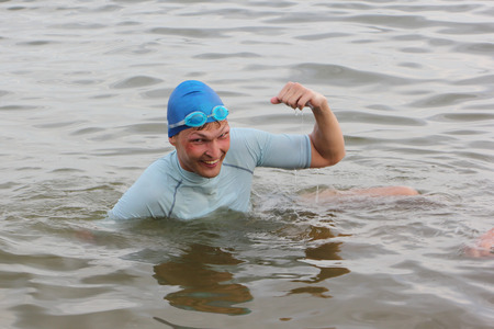 The swimmer in a blue cap rejoices to a victory Фото со стока
