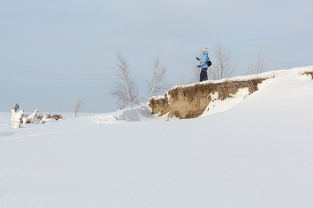 The woman the skier standing on the coast of the frozen river