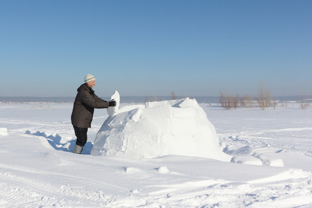Man building an igloo of snow blocks  on a glade in the winter Stock Photo