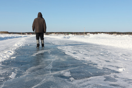 Man walking along a road of ice on the frozen reservoir in the winter, Ob River, Siberia, Russia Stock Photo