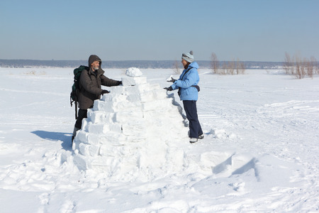 Man and woman building an igloo on a snow glade in the winter