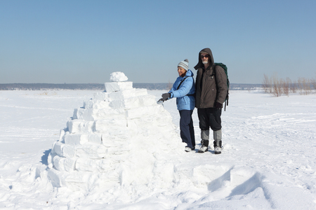 Man and woman standing to an igloo on a snow glade in the winter Stock Photo