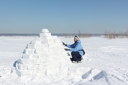 Woman in a blue jacket building an igloo on a snow glade in the winter Stock Photo