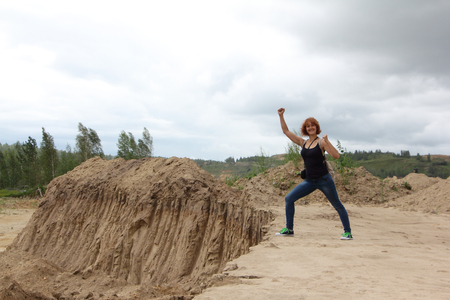 Woman standing at a sandpit in cloudy day, Novosibirsk Region, Russia