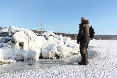 Man standing on a frozen river near stones with icicles, Ob Reservoir, Siberia, Russia Stock Photo