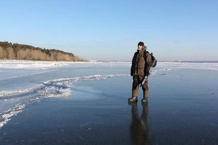 夕方、Ob 貯水池、シベリアで凍った川の薄氷を歩いて暖かい服の男