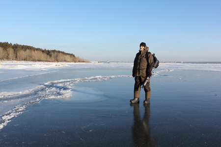 저녁에 얼어 붙은 강의 얇은 얼음을 따라 걷는 따뜻한 옷을 입은 남자, Ob 저장소, 시베리아