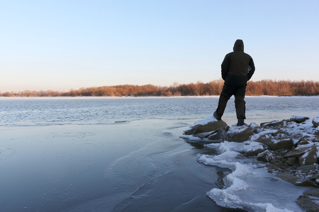 Man standing on stones at the freezing river at sunset, Ob River, Siberia, Russia 免版税图像