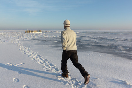 Mature man in a beige sweater running across the ice of a frozen river , Ob Reservoir, Russia