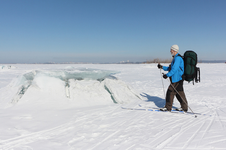 Man in a blue  jacket on ski looking at the ice breaking on the river,Ob Reservoir, Russia