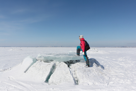 Happy woman in a red jacket stepping on an ice floe on a frozen river, Ob reservoir, Russia Stock Photo