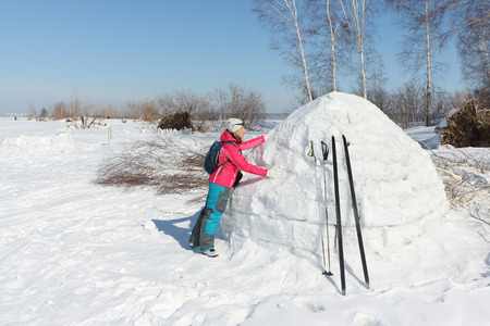 Happy woman skier in a red jacket standing near igloo on a snowy glade, Siberia, Russia Stock Photo