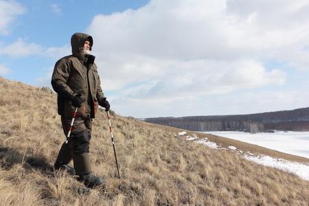 Nordic Walking - adult man descending from the mountain Bald, Bugotaksky hills, Novosibirsk region, Russia Stock Photo