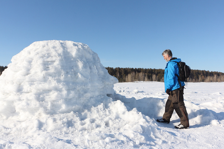 Man standing at the entrance an igloo on a snowy reservoir in winter, Novosibirsk, Russia