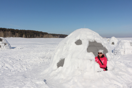 Happy woman in a red jacket sitting in an igloo   on a snowy glade Stock fotó