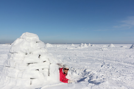 Happy woman in a red jacket lying in an igloo   on a snowy glade