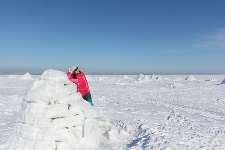 Happy woman in a red jacket standing near an igloo on a snowy glade