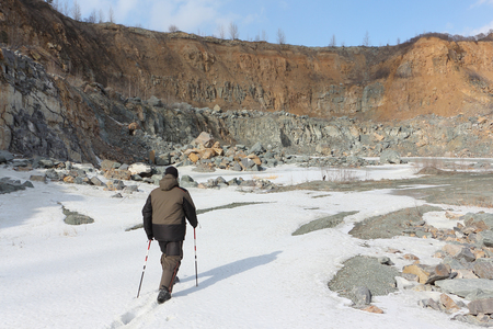 Man with sticks walking in quarry for the extraction of building stone, Novosibirsk Region, Russia Stock Photo