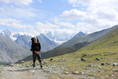 Man with a backpack standing on the pass Kara-Turek against the Belukha Mountain, Altai, Russia