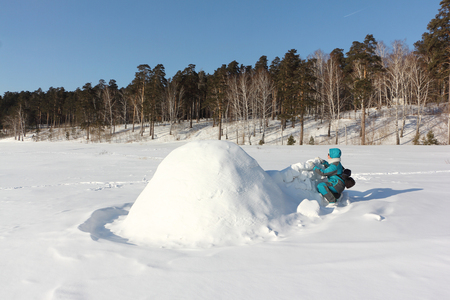 Happy woman in warm clothes building an igloo on a snow glade in the winter,  Siberia, Russia