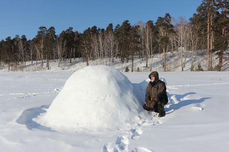 Man in warm clothes sitting by an igloo on a glade in the winter, Siberia, Russia