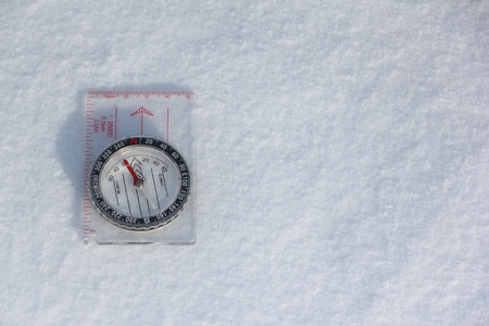 Compass lying on the snow in winter