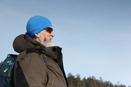 Male traveler with a beard in a blue hat and sunglasses against the blue sky