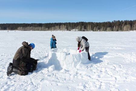 Happy grandfather, grandmother and grandson building an igloo on a snowy glade in winter