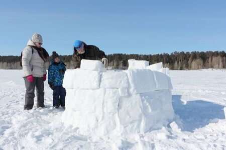 Happy grandfather, grandmother and grandson building an igloo on a snowy glade in winter, Novosibirsk, Russia
