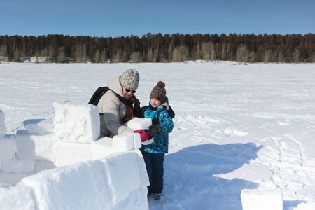 Happy grandmother and grandson building an igloo on a snowy glade in winter, Novosibirsk, Russia Zdjęcie Seryjne