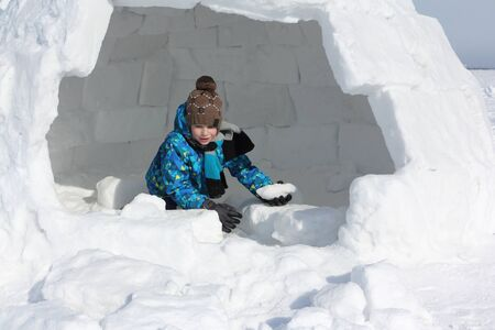 Happy cheerful boy building an igloo in winter