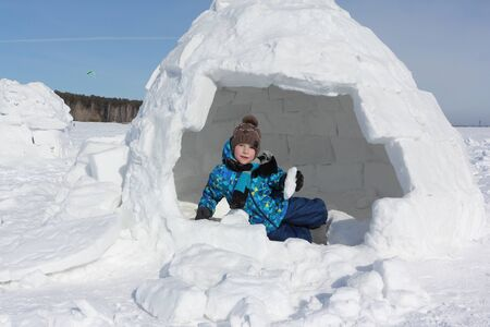 Happy cheerful boy with a piece of snow in his hands sitting an igloo in winter Stock fotó