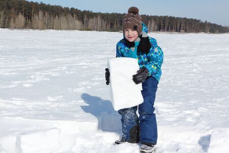 Happy cheerful boy lifting a snow block for building an igloo