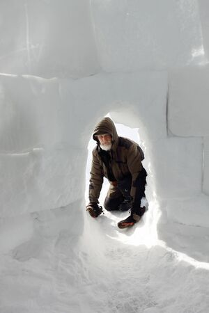 Man in warm clothes at the entrance to the igloo in winter