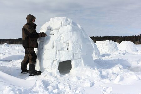 Man building an igloo from snow blocks in the winter, Novosibirsk, Russia Zdjęcie Seryjne