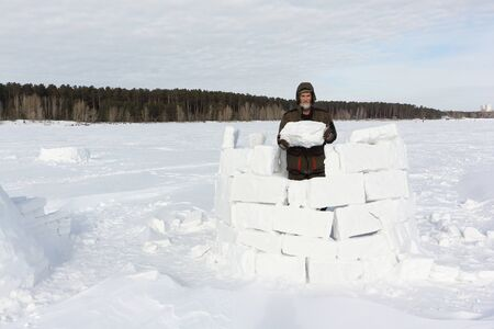 Man building an igloo from snow blocks in the winter, Novosibirsk, Russia