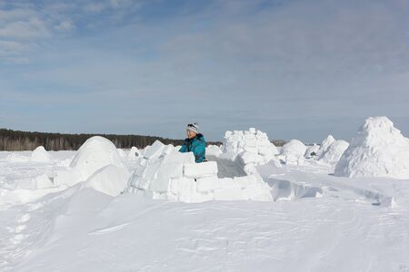 Happy woman in warm clothes building an igloo on a snow glade in the winter,  Novosibirsk, Russia