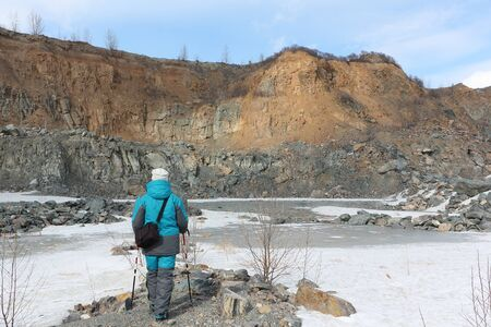 Woman standing in a quarry for the extraction of building stone, Bugotak Hills, Novosibirsk region, Russia