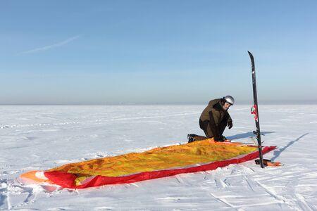 Man unwinding slings at kite on snow, Ob reservoir, Novosibirsk, ,Russia