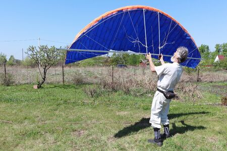 Man learns to manage homemade kitewing on the lawn in summer